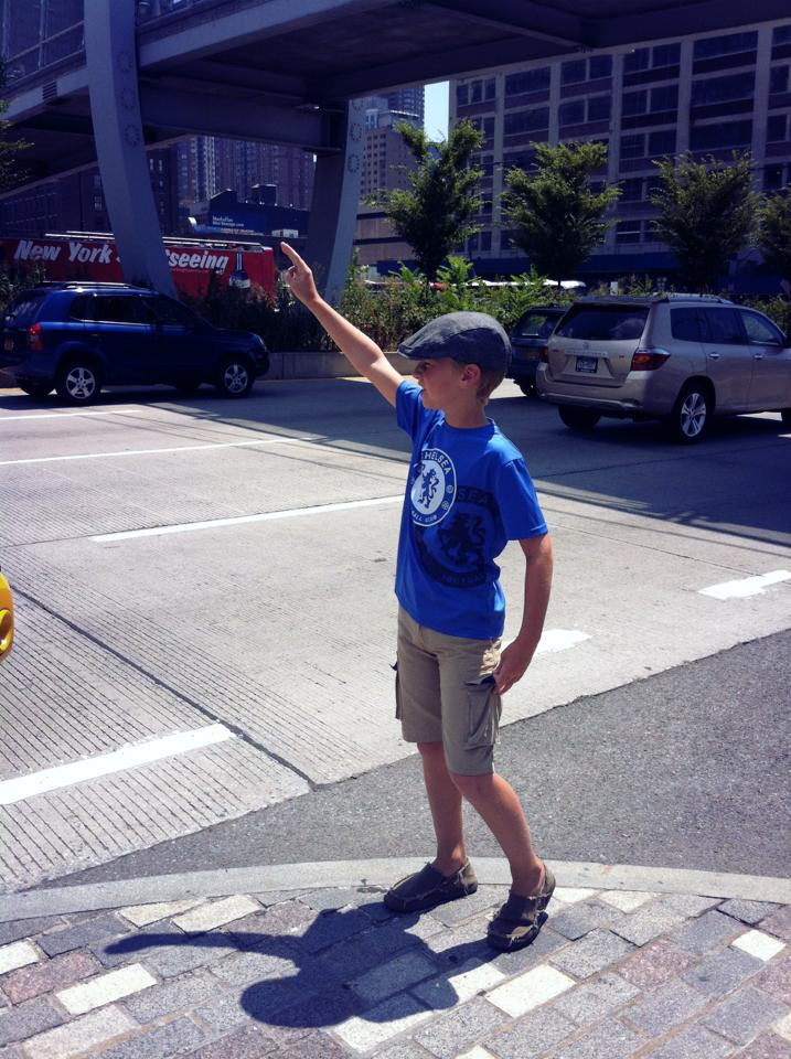 Hailing a taxi in his Newsies cap. We may have a future city kid on our hands.